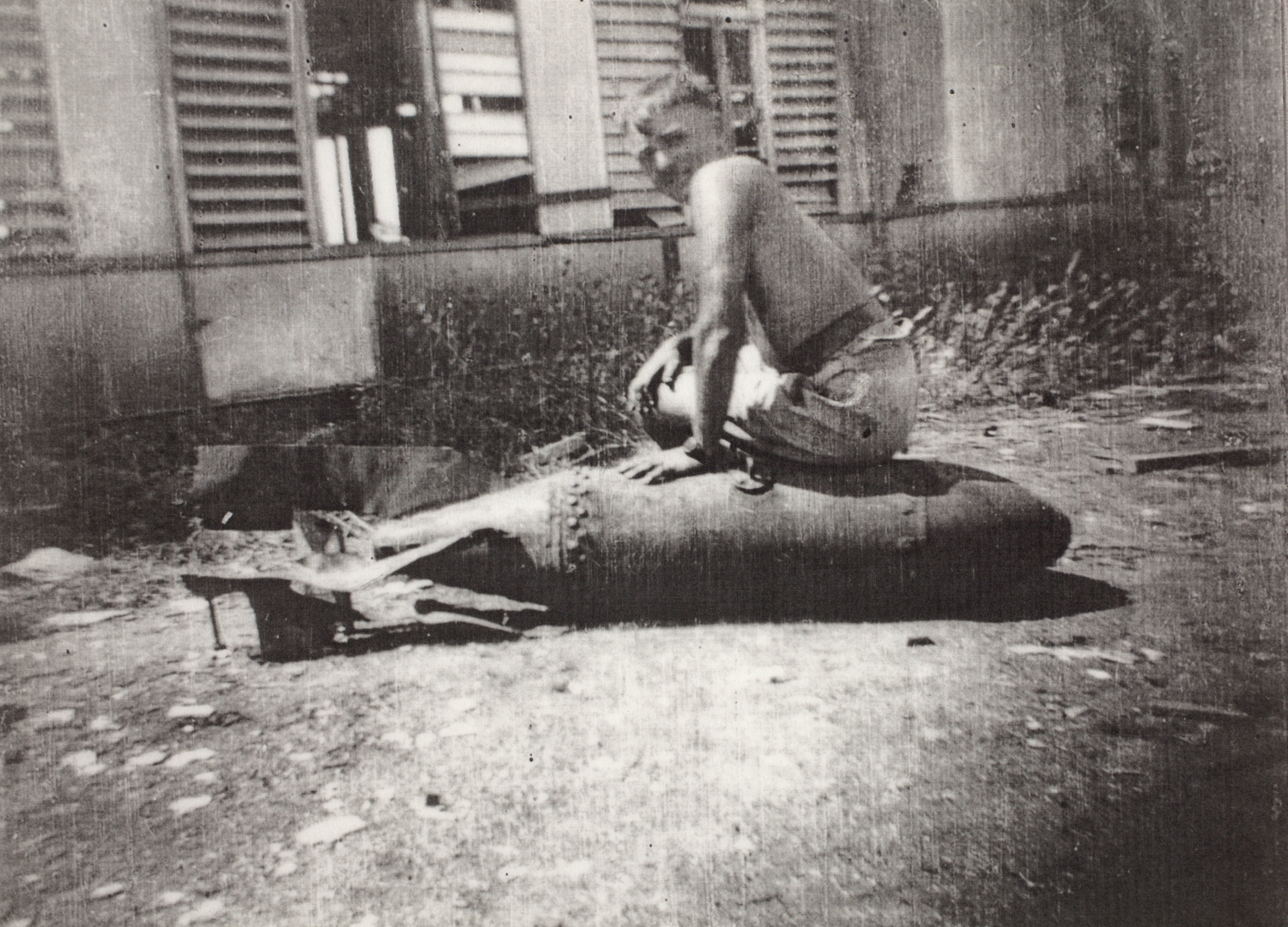 George A. Marven astride a defused unexploded 250 pound Japanese bomb